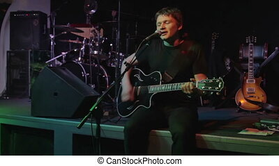 Rock singer on stage - Man plays guitar and sings on stage
