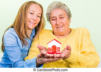 Home insurance - Elderly woman and daughter holding a...
