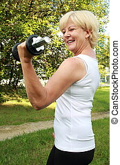 Elderly woman doing outdoor training with dumbbell