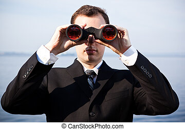 Caucasian businessman with binoculars - A portrait of a...