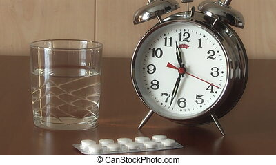 Alarm Clock and Pills on the table, medicine and curing...