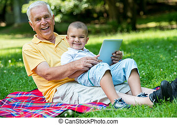 grandfather and child in park using tablet - grandfather and...
