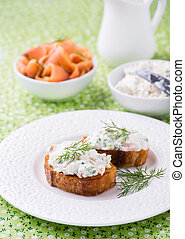 Canape with soft cheese spread on white plate, selective...