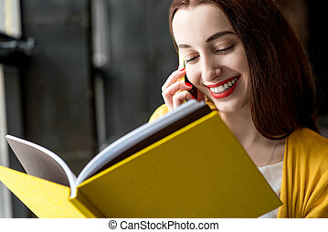 Woman with book and mobile phone - Young smiling woman...