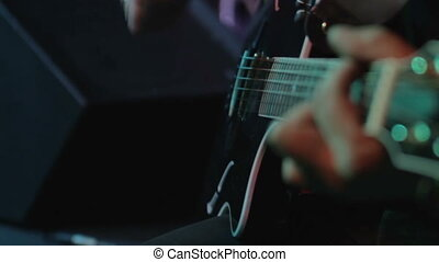 Electro-acoustic guitar closeup - Playing the guitar using a...