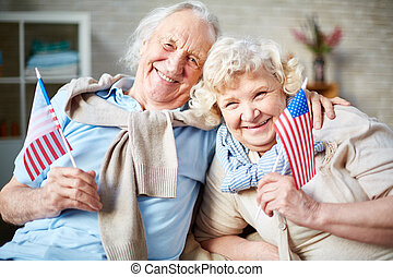 Senior patriots - Smiling seniors with American flags