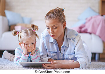 Online education - Young woman teaching her daughter at home