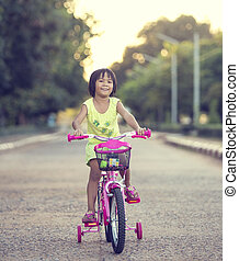 Cute smiling little girl with bicycle on road