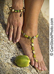 Female feet and hand with bracelets against the stone