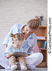 Networking at leisure - Young woman and her cute daughter...