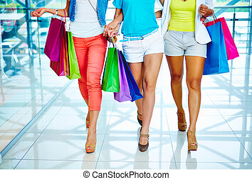Legs of shopaholics - Legs of three consumers with paperbags...