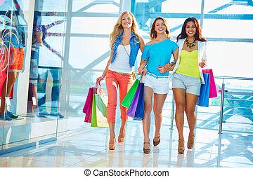 Shoppers in the mall - Friendly consumers with paperbags...