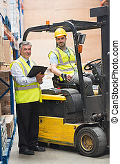 Driver operating forklift machine next to his manager in...