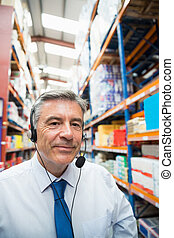 Warehouse manager giving orders on headset in a large...