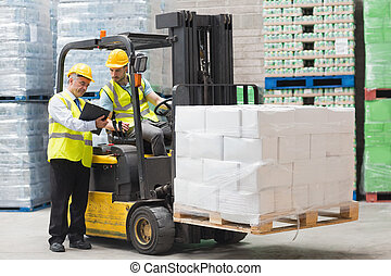 Forklift driver talking with his manager in a large...