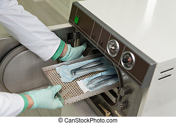 Dentist Places Medical Autoclave For Sterilising Surgical -...
