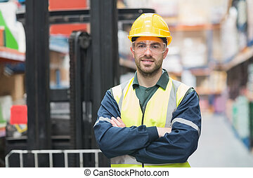 Manual worker wearing hardhat and eyewear in warehouse