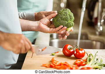 Mature couple preparing vegetables together at home in the...