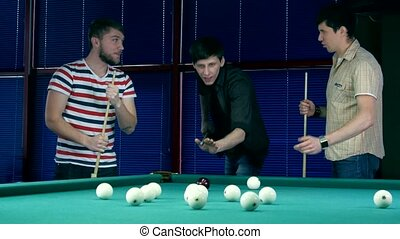 Several young men discussing game of billiards. One of the...