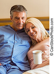 Happy mature couple smiling at camera on bed at home in...
