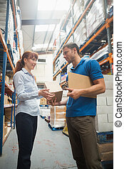 Delivery man passing parcel to warehouse manager