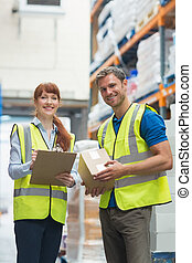 Smiling warehouse manager and delivery man