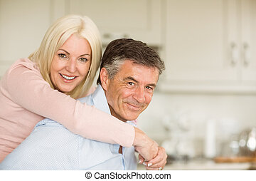 Happy mature couple smiling together at home in the kitchen