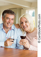 Happy mature couple drinking red wine at home in the kitchen