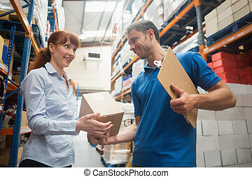 Delivery man passing parcel to warehouse manager in...