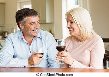 Happy couple drinking red wine - Happy mature couple...