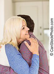 Happy mature couple hugging each other at home in the...
