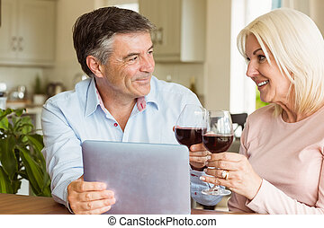 Happy mature couple using tablet drinking red wine at home...
