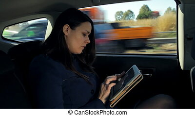 business woman in taxi working - Serious woman working while...