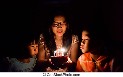 Happy Family Blowing Candles On Birthday Cake Together