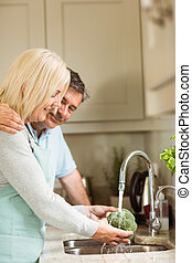 Mature couple washing broccoli