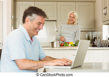 Happy mature man using laptop while wife prepares vegetables...