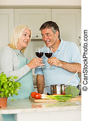 Happy mature couple having red wine while making dinner at...