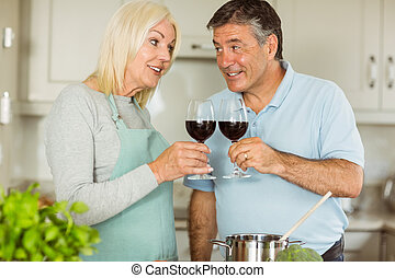 Happy mature couple making dinner together at home in the...