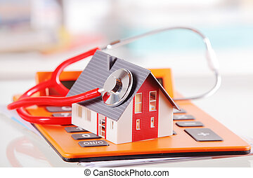 Model House with Stethoscope on Calculator Device -...