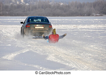 the car carrying the man on ice-boat in tow in the snow