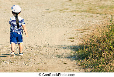 Sweet toddler dressed as a sailor walking with determination on