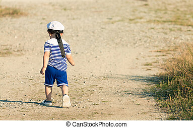 Toddler dressed as a sailor walking with determination on a grav