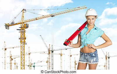 Woman in hard hat with large builders level on her shoulder,...