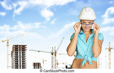 Woman in hard hat adjusting protective glasses, looking at...