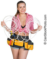 Woman in tool belt holding coils of cable, looking at...