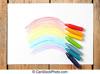 Oil pastel crayons lying on a paper with painted rainbow -...