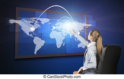Businesswoman operating touch screen interface featuring...