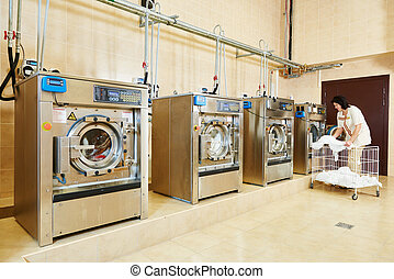 Laundry service - cleaning services. Woman loading laundry...