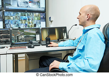 Security video surveillance - security guard watching video...