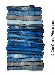 high stack of various shades of blue jeans on a white...